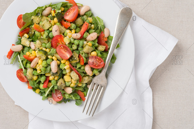 Summer succotash plate set with metal fork and white napkin.