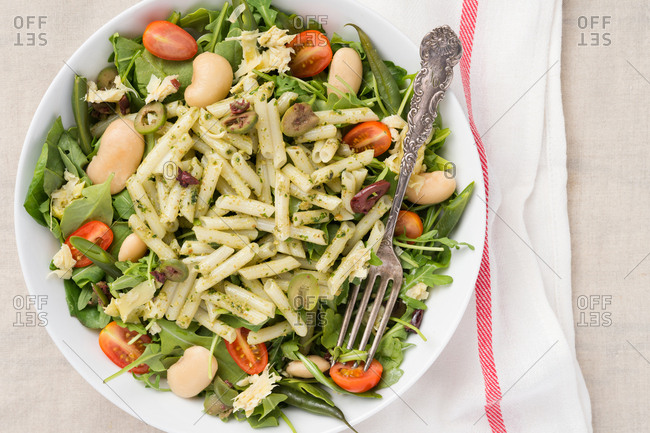 Penne pasta pesto salad in a white bowl with a metal fork. Set on a napkin.