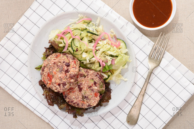Vegan bean burgers and salad on a white plate and a small bowl of salsa.
