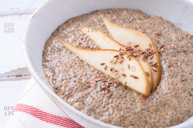 Pear and spice chia pudding in a white bowl on a napkin sitting on a white wooden table.