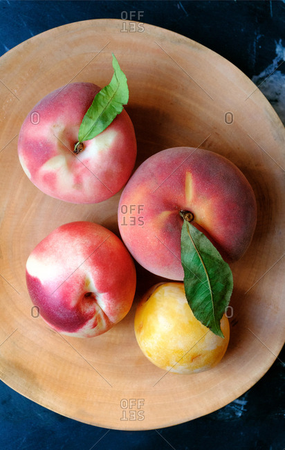 Peaches and plums in wooden bowl