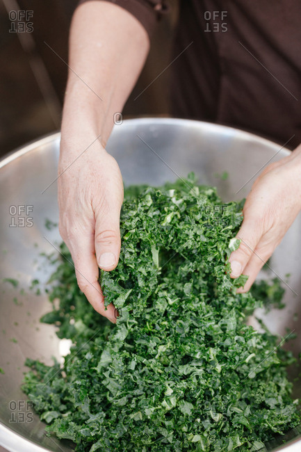 Chefs hands tossing a kale salad