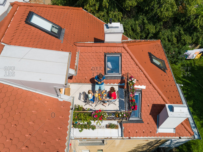 Aerial view of family having breakfast on rooftop balcony in morning sun in Spring.