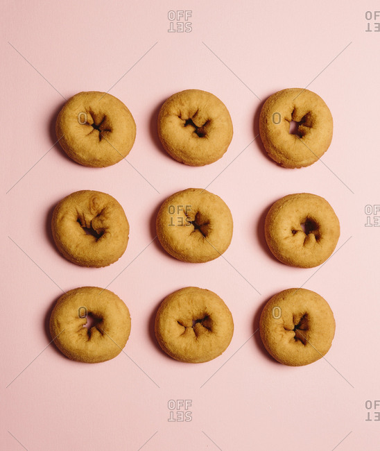 Top view of plain donuts on a light pink background