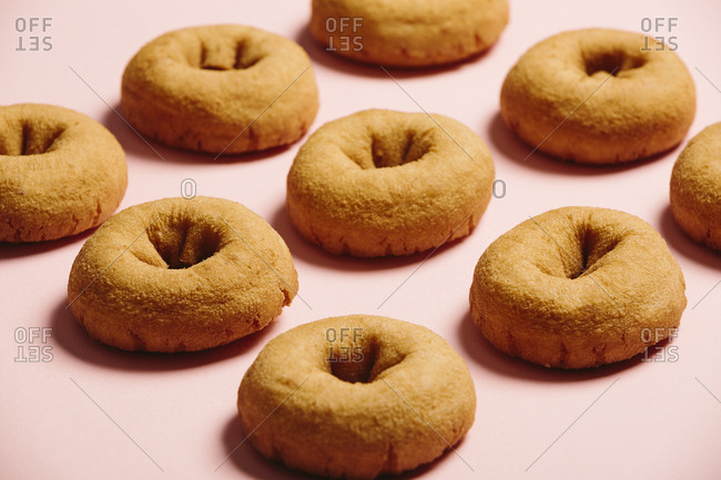 Closeup of plain donuts on a light pink background