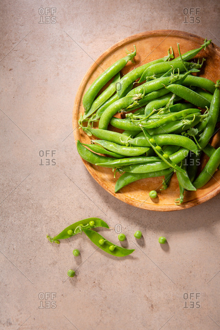 Fresh green pea pods on a wooden plate