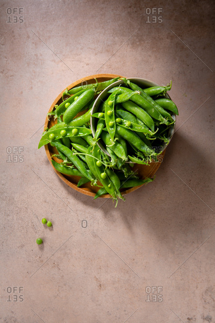 Fresh green pea pods on a wooden plate top view