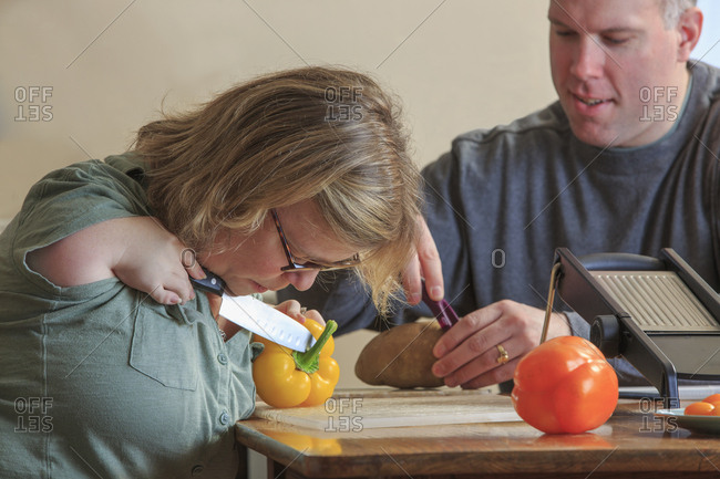 Woman with TAR Syndrome cutting vegetables with her husband in the kitchen.