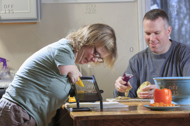 Woman with TAR Syndrome grating vegetables with her husband in the kitchen.