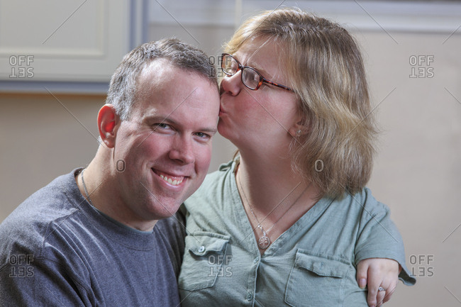 Woman with TAR Syndrome kissing her husband.