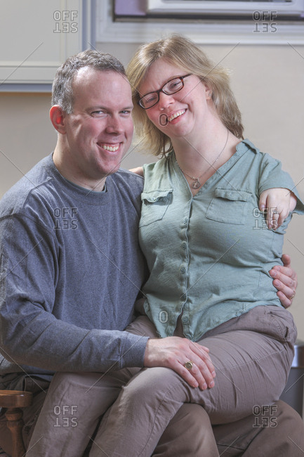 Woman with TAR Syndrome sitting on her husband's lap.