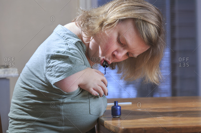 Woman with TAR Syndrome painting her nails at home.