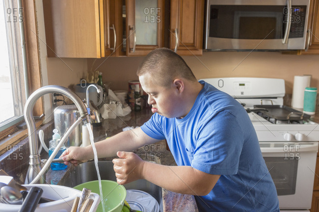 Teen with Down Syndrome doing dishes.