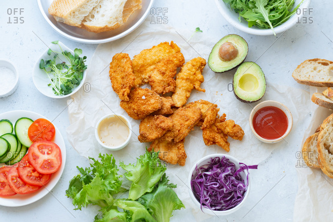 Fried chicken slices with avocado, salad, bread and healthy vegetables