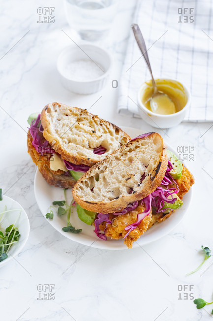Lunch sandwich with avocado, fried chicken and sliced red cabbage served with mustard sauce