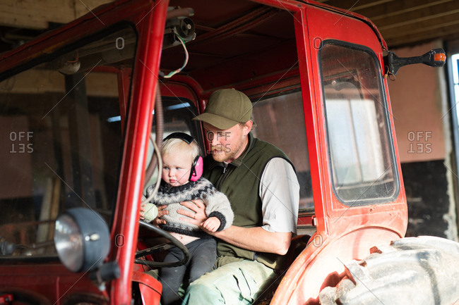 Man holding baby girl on a tractor