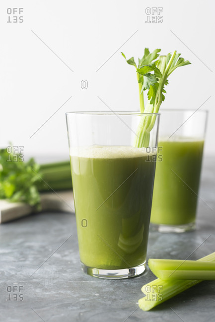 Two glasses of celery juice garnished with celery stalks