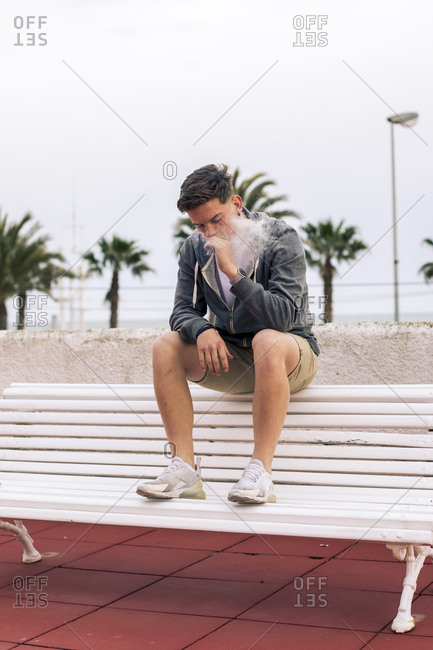 Young man smoking a joint with palm trees in the background
