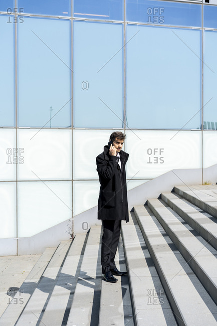 Businessman on cell phone on stairs in the city