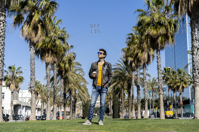 Spain- Barcelona- man standing on lawn in the city looking around