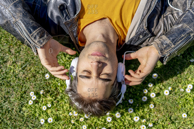 Man lying on flower meadow with headphones
