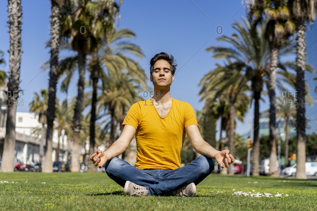Spain- Barcelona- man practicing yoga on lawn in the city