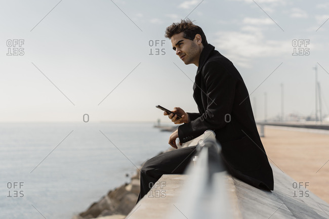 Businessman sitting on quay wall with cell phone