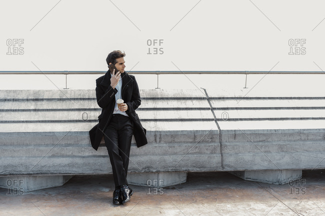Businessman with takeaway coffee on cell phone outdoors