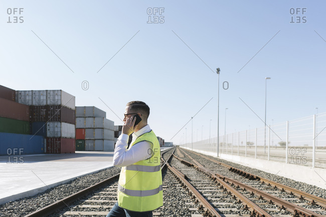 Man on railway tracks in front of cargo containers talking on cell phone