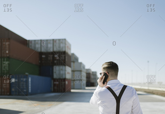 Rear view of manager talking on cell phone in front of cargo containers on industrial site