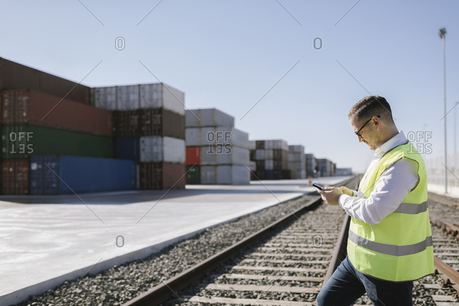 Man on railway tracks in front of cargo containers using cell phone