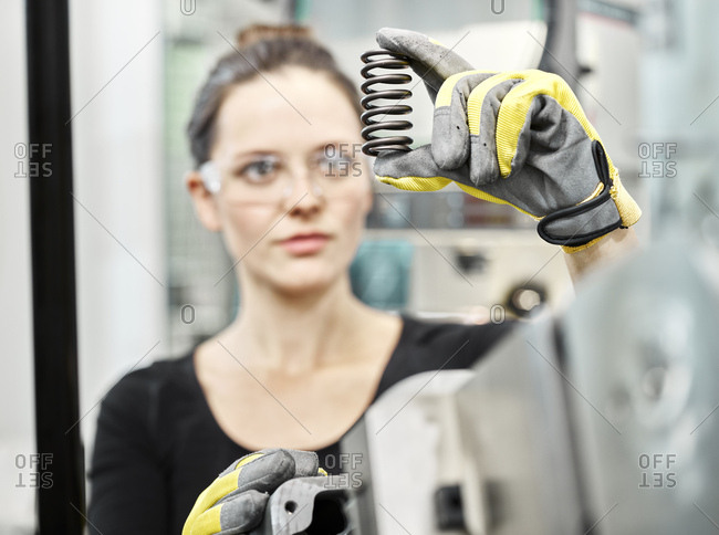 Woman working on a machine- looking on spring