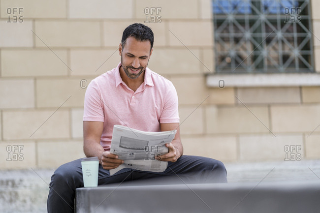 Man with takeaway coffee reading newspaper in the city