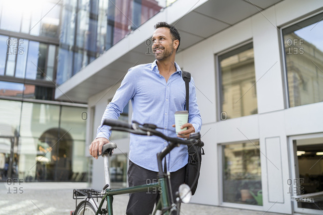 Businessman with bicycle on the go in the city