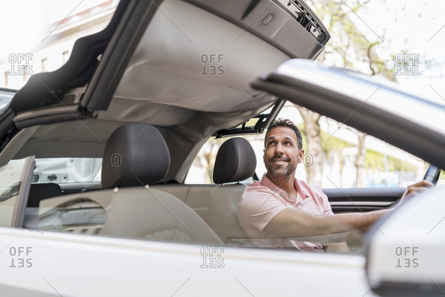 Man sitting in car with closing convertible top