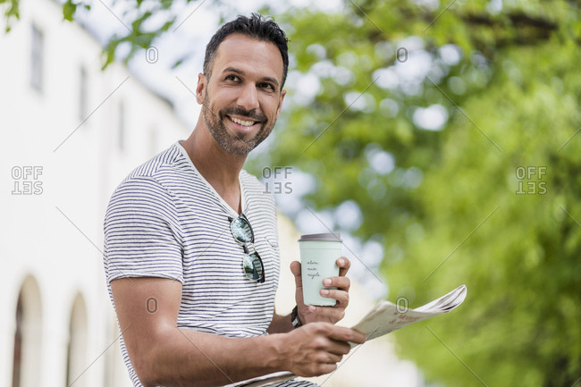 Smiling man with takeaway coffee and newspaper in a park