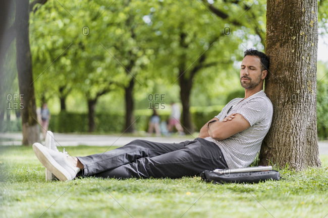 Man leaning against a tree in park having a nap