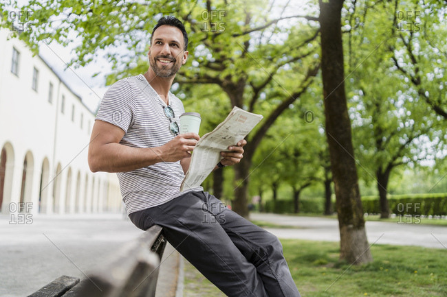 Smiling man with takeaway coffee and newspaper on park bench