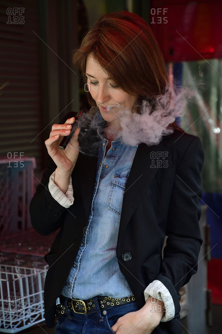 Portrait of a mature woman- smoking electronic cigarette