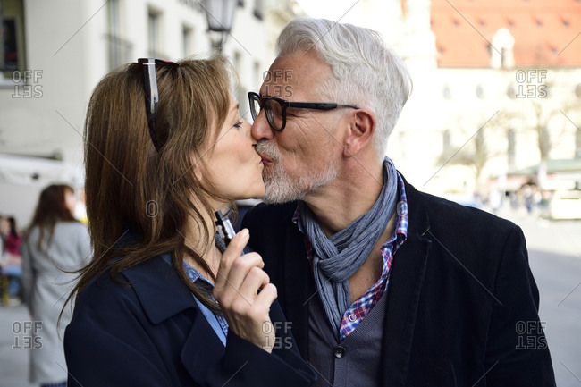 Mature couple walking in the city- woman smoking electronic cigarette
