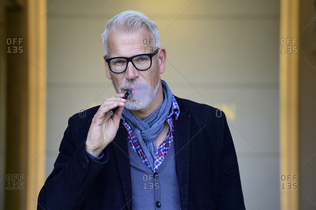 Portrait of a mature man- smoking electronic cigarette