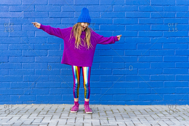 Girl wearing blue cap and oversized pink pullover standing in front of blue wall singing