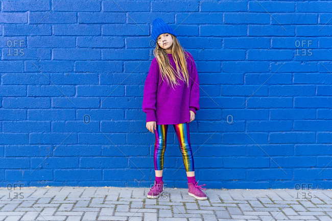 Portrait of girl wearing blue cap and oversized pink pullover standing in front of blue wall