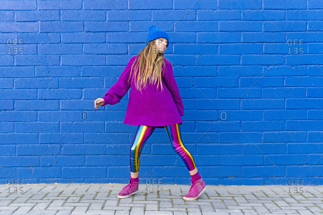 Portrait of girl wearing blue cap and oversized pink pullover standing in front of blue wall dancing