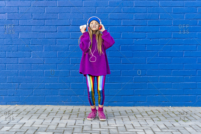 Girl wearing blue cap and oversized pink pullover standing in front of blue wall listening music with headphones