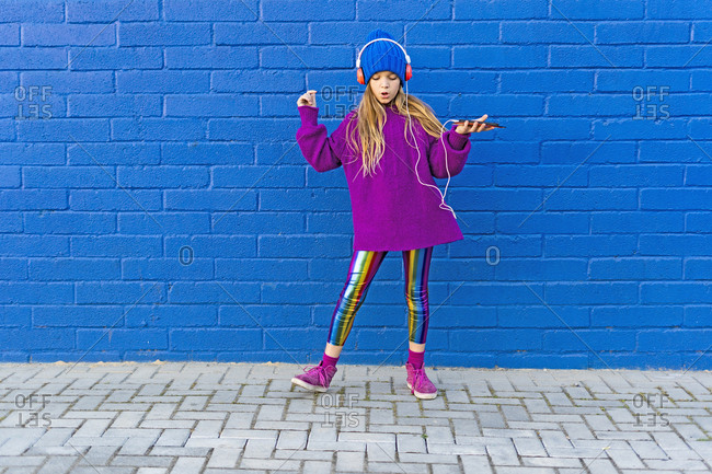Girl wearing blue cap and oversized pink pullover listening music with headphones in front of blue wall