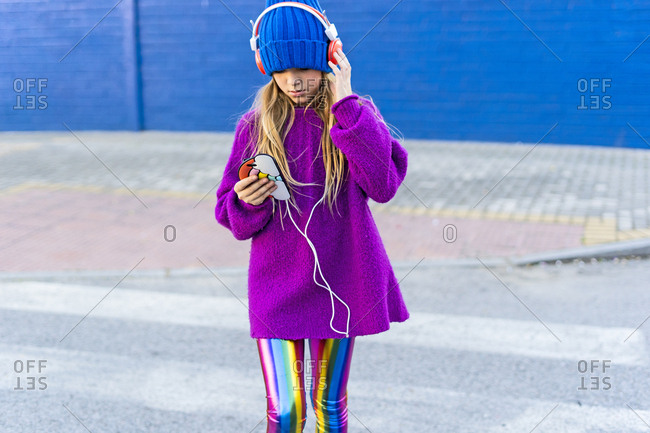Girl wearing blue cap and oversized pink pullover listening music with headphones and smartphone