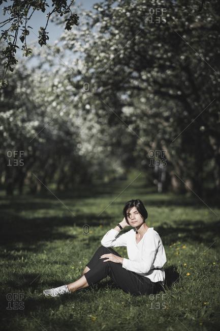 Woman sitting on meadow between apple trees
