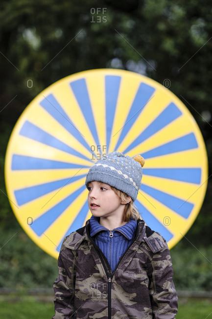 Portrait of boy wearing warm clothing standing in front of yellow and blue circle