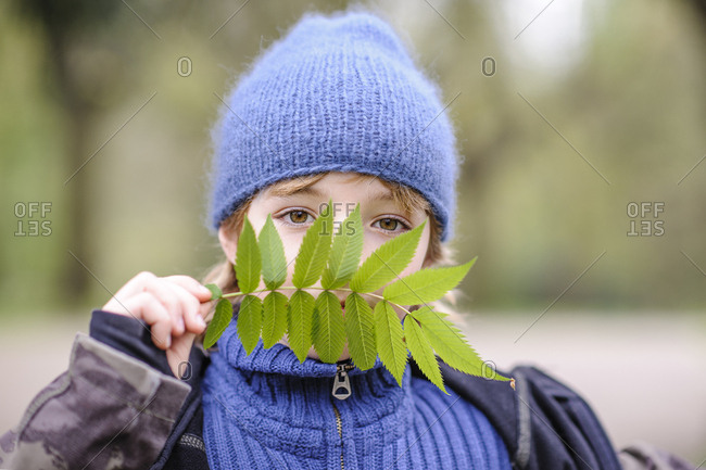 Portrait boy wearing blue hat and sweater looking through green leaf